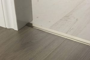 Floating Euro door threshold stuck donw in doorway, connecting laminate flooring