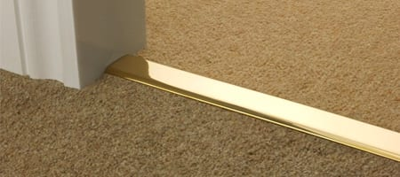 Polished brass carpet to carpet door bar joining two brown carpets in doorway