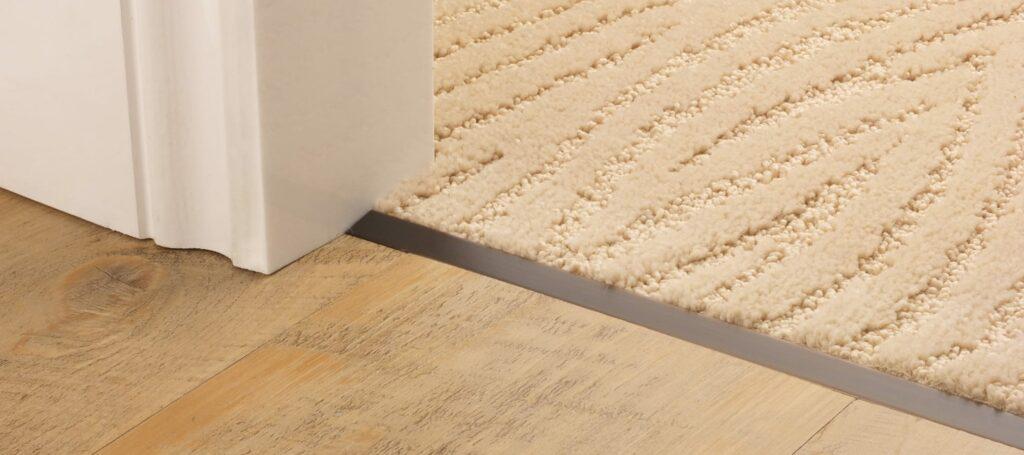 Z bar joining carpet to wooden floor in doorway, antique bronze