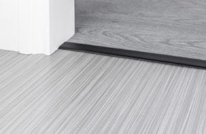 Black Premier Z4 door threshold strip joining a thin flatweave carpet to a wood floor