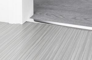 Chrome Premier Z4 door threshold strip joining a thin flatweave carpet to a wood floor