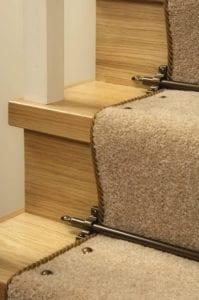 carpet studs antique brass attached to beige stair runner