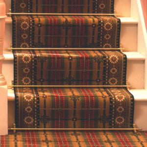 Lancaster carpet rods in polished brass fitted on tartan stair runner