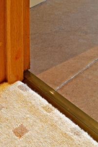 Posh door thresholds fitted between patterned beige carpet and tiles