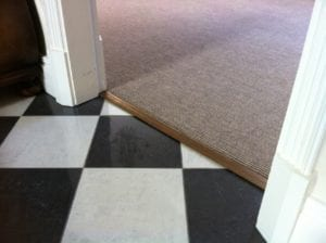 Posh door bar in antique brass joins carpet to LVT flooring in black and white