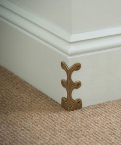 Antique brass coloured Skiffer skirting board corner protector on painted skirting