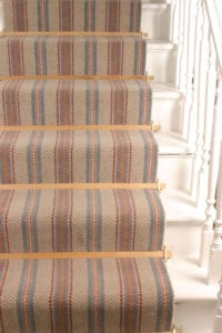 Tudor carpet wooden rod bars in light finish and brass trims fitted on striped stair carpet