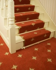 Wooden oak coloured stair rods with metal trim fitted on red stair runner