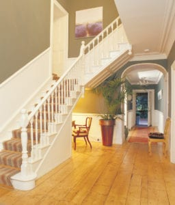 Grand white painted staircase fitted with striped runner and wooden Tudor stair rods