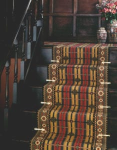 Period dark wood staircase fitted with tartan stair runner & Victorian brass stair clips