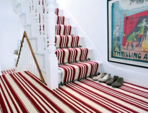 Arrow design of carpet rods for runners fitted on red & cream striped stair runner
