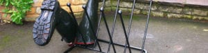 Wrought iron wellington boot rack holding 5 pairs of boots in garden