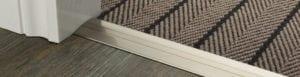 Posh door threshold in satin brass joining striped carpet to wood