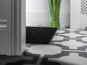 Metal matwell framed with black matwell edging installed on tiled hall floor