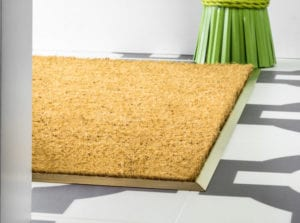 Satin brass mat well trim installed on tiled hall floor