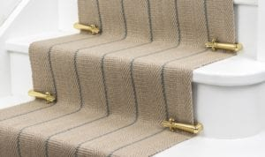 Victorian Stair Clips in polished brass on striped stair runner