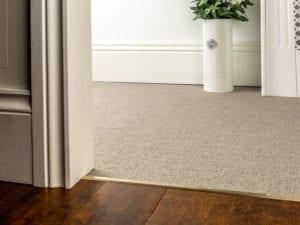 Premier Slim z bar joining a beige carpet to wood tiles, slim, satin brass