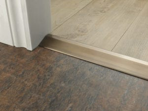 Button to choose door bar ramp that transitions from one floor level to another, antique brass