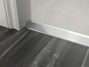 Door bar ramp that transitions from one floor level to another in brushed chrome