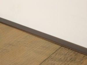 Self adhesive bronze door bar joining wood to tiled floor