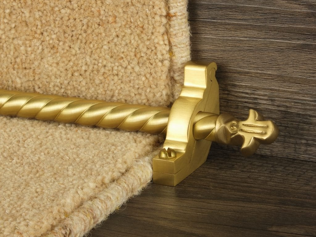 Spiral rod in polished brass contrasts with plain beige carpet