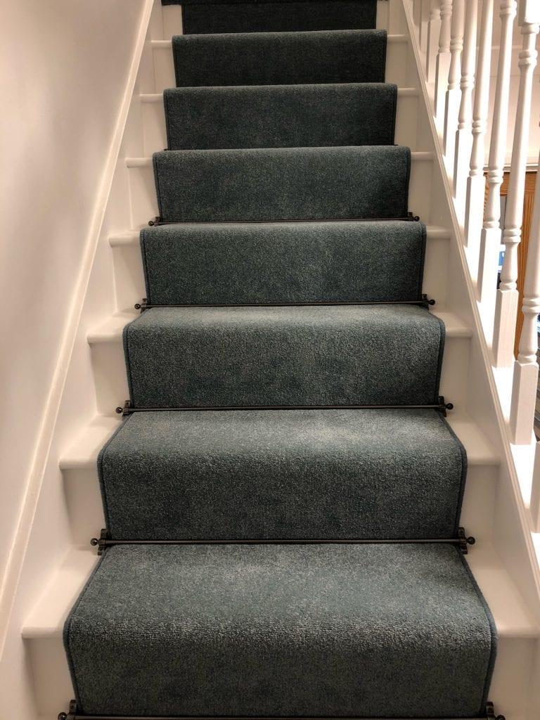 Black stair rods for carpet runners fitted on teal carpet runner
