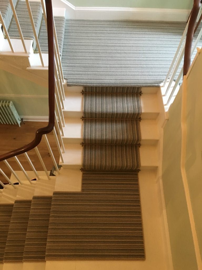 Antique brass stair rods on striped stair runner
