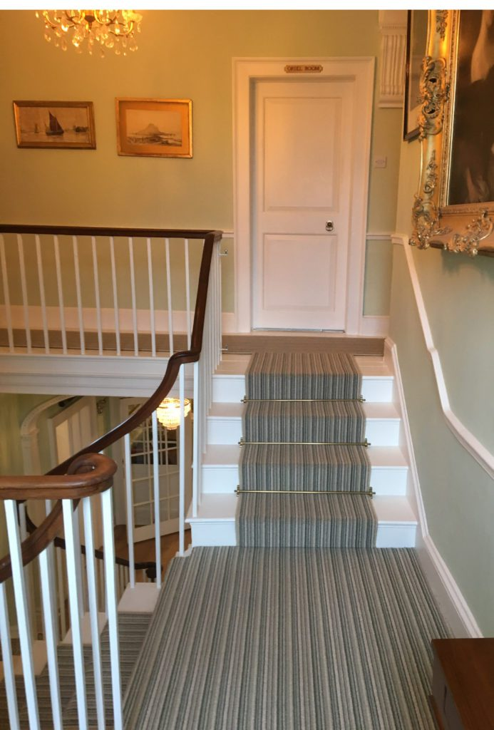 Polished brass stair carpet rods on striped runner, sweeping stairs
