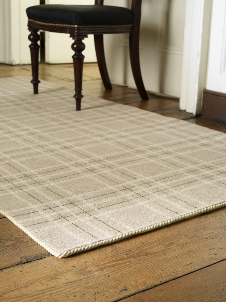 carpet edge binding in beige on a tartan rug with wooden chair