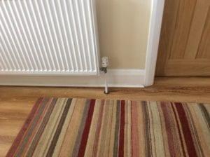 Circular design pipe cover around radiator pipe, striped rug