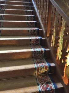 Period staircase fitted with tarnished antique brass stair rods