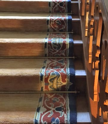Antique brass stair rods featured on a period wide staircase