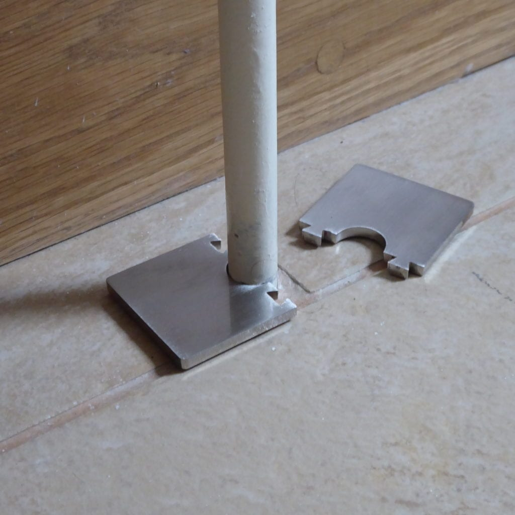 Oblong pipe collar clips together around the radiator pipe on the tiled floor