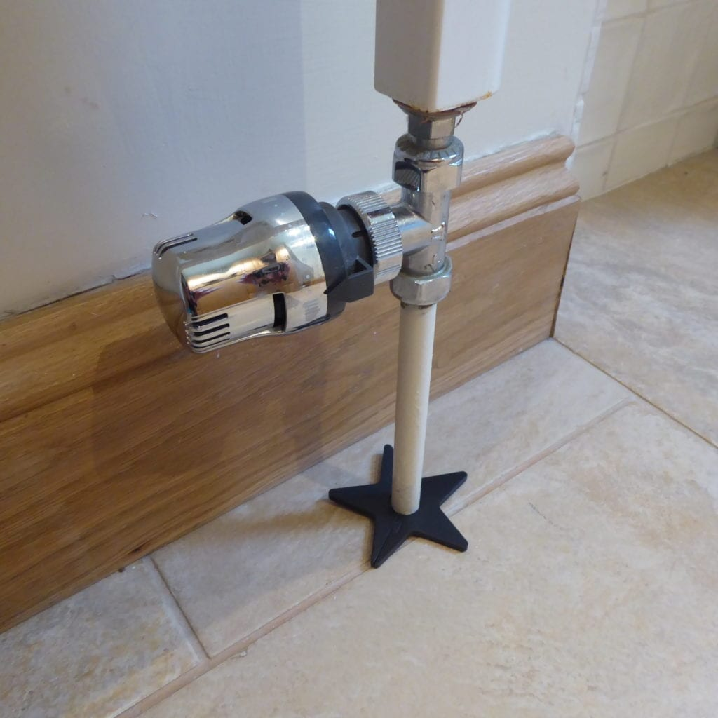 Black star-shaped pipe collar to cover up gap around pipe in floor