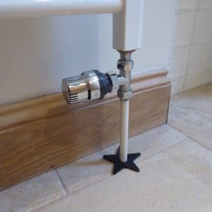 Star-shaped pipe cover on tiled floor around bottom of radiator pipe