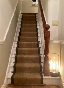 Dark wood stair rods on a sisal stair runner