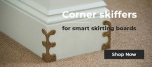 Antique brass skirting corner protectors fitted to white skirting board