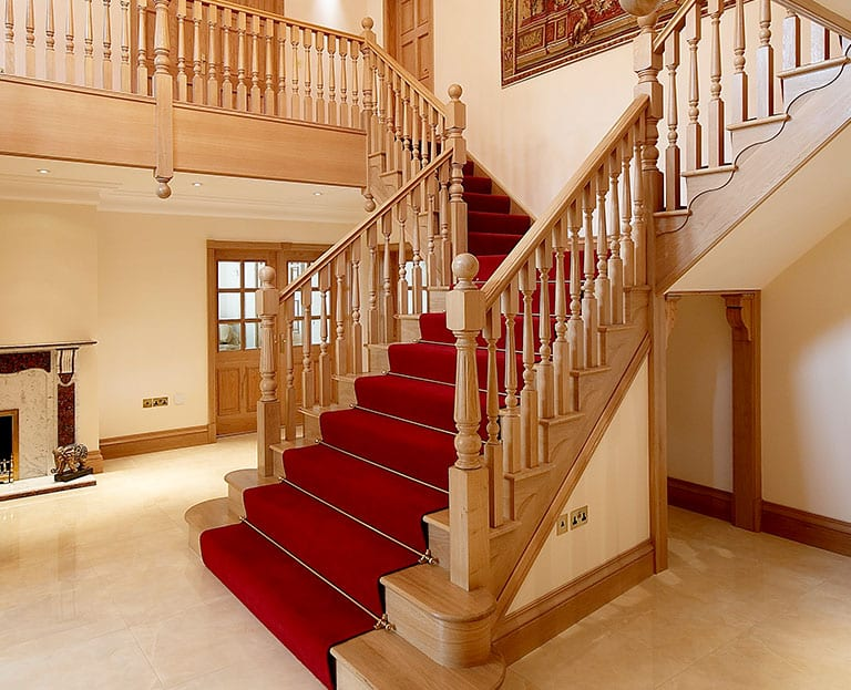 Wooden staircase with red carpet and stair rods