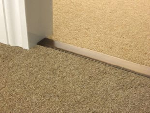 Carpet door thresholds joining beige carpets in antique brass