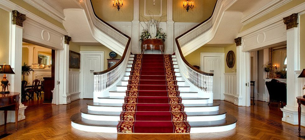 Bordered red stair runner onstatement staircase with brass stair rods