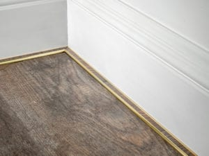 scotia moulding in antique brass attached to skirting board