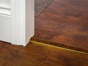 Vinyl flooring threshold strip in brass to match flooring