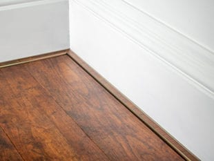 vinyl floor trim in antique brass attached to skirting board
