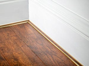 scotia trim in brass shown attached to skirting board