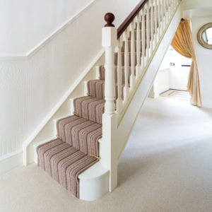 Polished brass stair clips fitted to stair runner on striped carpet